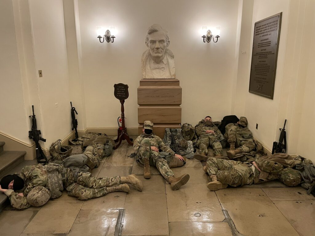 a photo by the NY Times' Erin Schaff showing six national guard troops sleeping on the floor of a hallway in the US capitol on Jan 11, 2021, under a large marble bust of Abraham Lincoln and a bronze plaque commemorating the last time troops slept in the Capitol to guard it, at the outset of the Civil War.