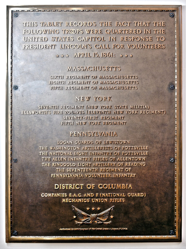 a bronze plaque with raised text listing the regiments that quartered in the us capitol after Lincoln's call for volunteers on April 15, 1861, which was installed in 1964